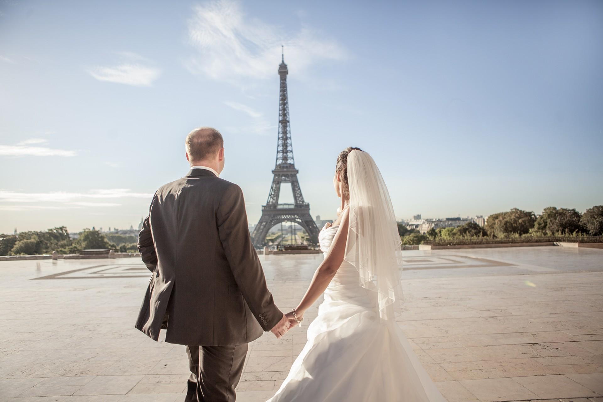 Hochzeitspaar blickt auf den Eiffelturm